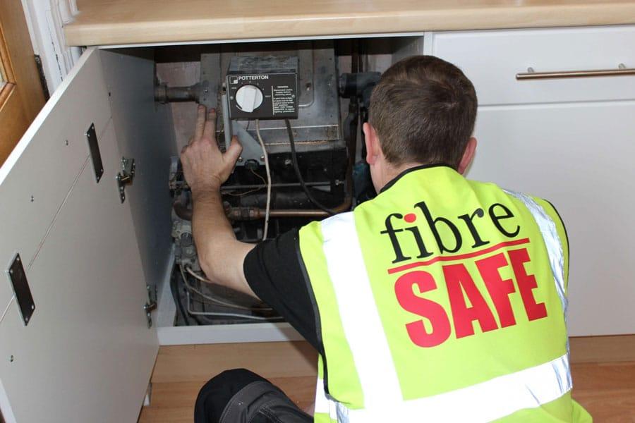 Fibre safe worker working on boiler